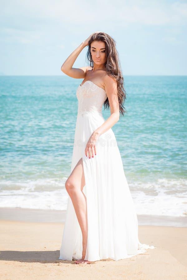Forme a noiva que anda abaixo da praia em um vestido branco A menina bonita anda pena descalça a praia foto de stock royalty free