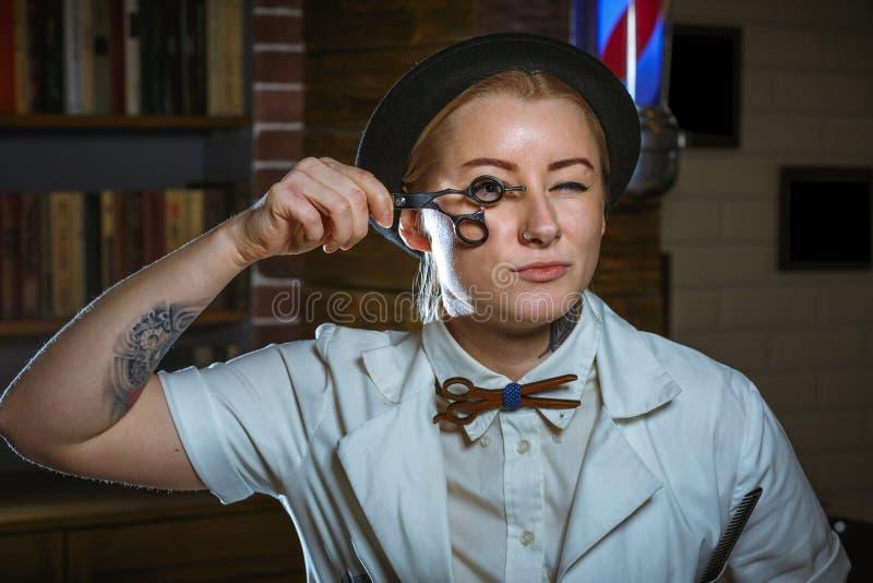 Forme o barbeiro do barbeiro da mulher com tesouras à disposição nos vagabundos fotografia de stock royalty free