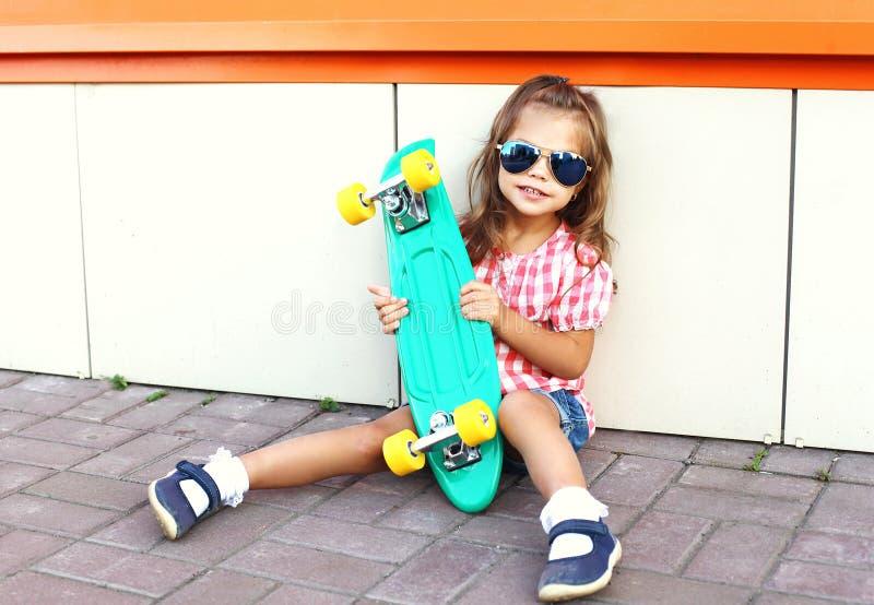 Forme o conceito da criança - criança à moda da menina com os óculos de sol vestindo do skate na cidade fotografia de stock royalty free