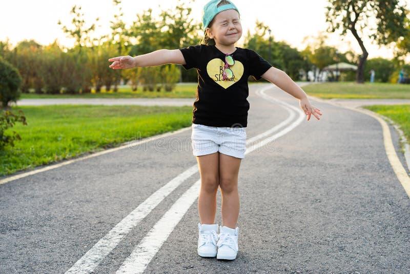 Forme o conceito da criança - retrato da criança bonito pequena à moda da menina que veste um tampão fora na cidade imagem de stock royalty free