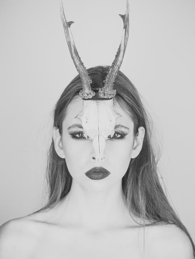 Forme o diabo da menina místico do curandeiro com chifres Mulher com composição e chifres Olhar e cosméticos da beleza para o ski fotos de stock royalty free