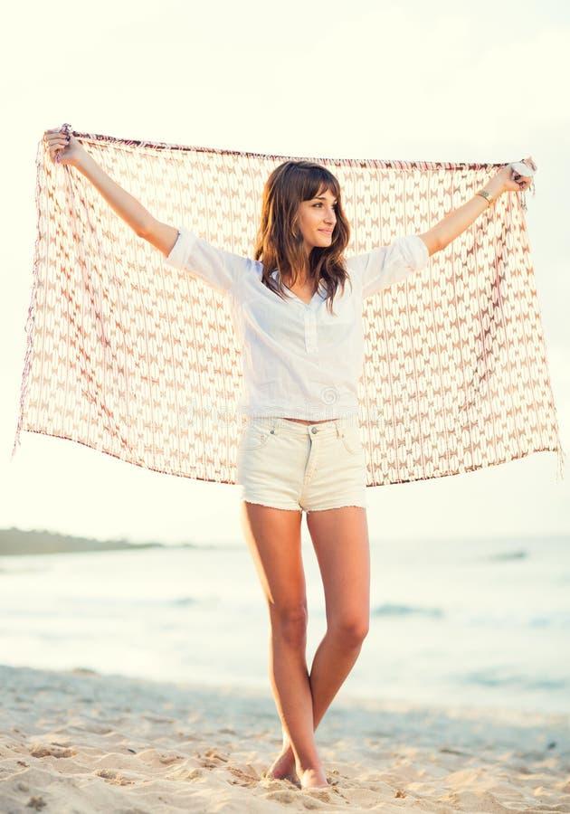 Forme o estilo de vida, jovem mulher bonita na praia no por do sol foto de stock