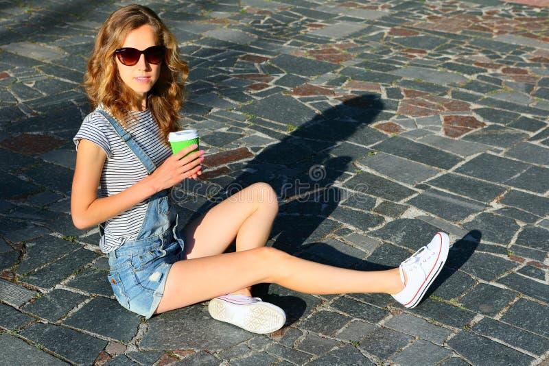Forme o estilo do moderno da mulher loura com um copo de café descartável imagem de stock royalty free