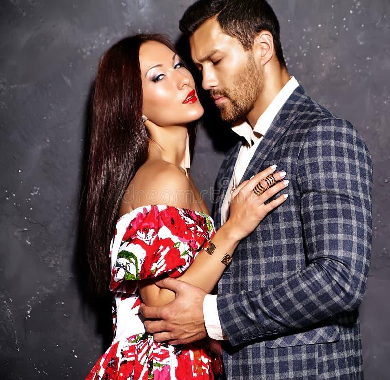 Forme o homem elegante considerável no terno com a mulher 'sexy' bonita que levanta perto da parede cinzenta imagens de stock royalty free