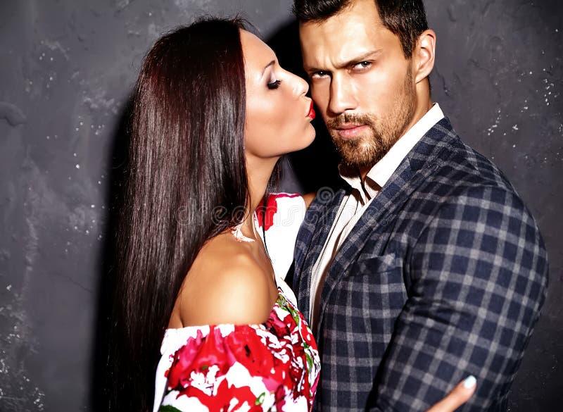 Forme o homem elegante considerável no terno com a mulher 'sexy' bonita que levanta perto da parede cinzenta fotografia de stock