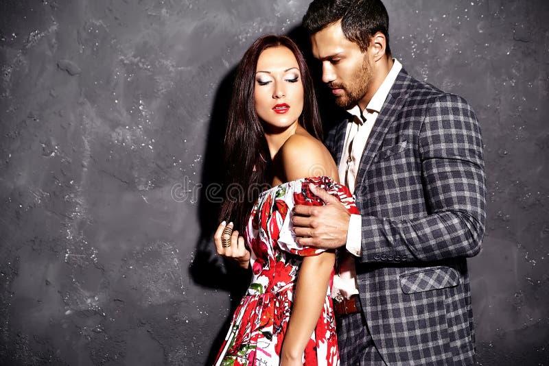 Forme o homem elegante considerável no terno com a mulher 'sexy' bonita que levanta perto da parede cinzenta fotos de stock royalty free