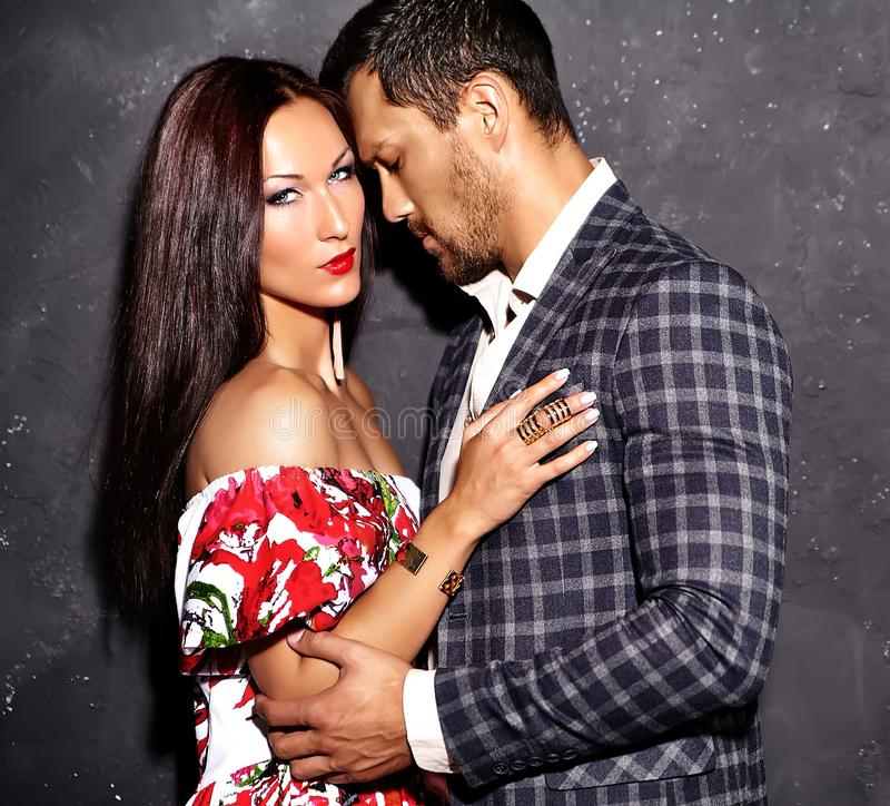 Forme o homem elegante considerável no terno com a mulher 'sexy' bonita que levanta perto da parede cinzenta imagem de stock