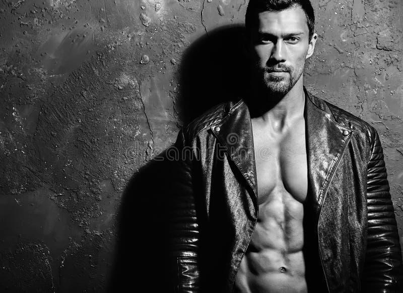 Forme o homem modelo masculino vestido no casaco de cabedal preto do motociclista que levanta no estúdio na parede cinzenta do gr fotos de stock