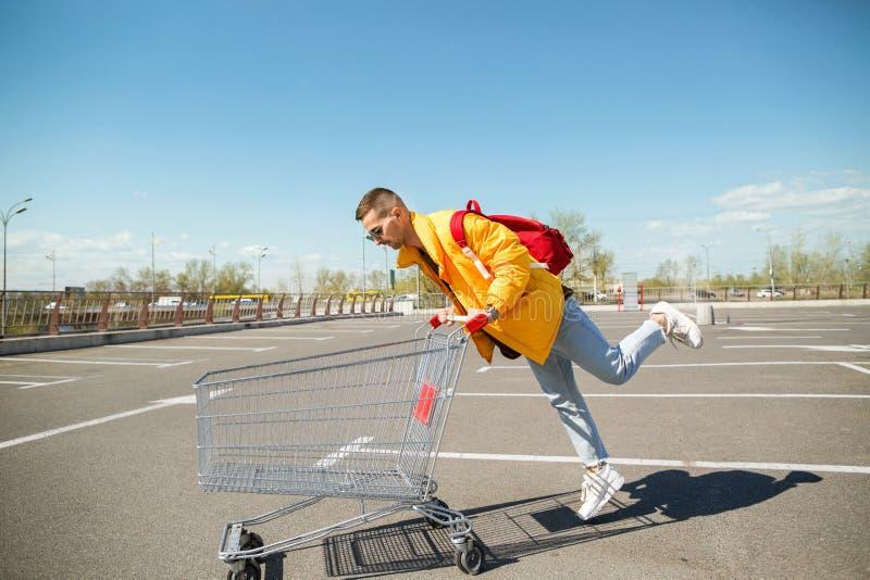 Forme o indivíduo nos óculos de sol e em um revestimento amarelo um carro do alimento no estacionamento do supermercado fotos de stock