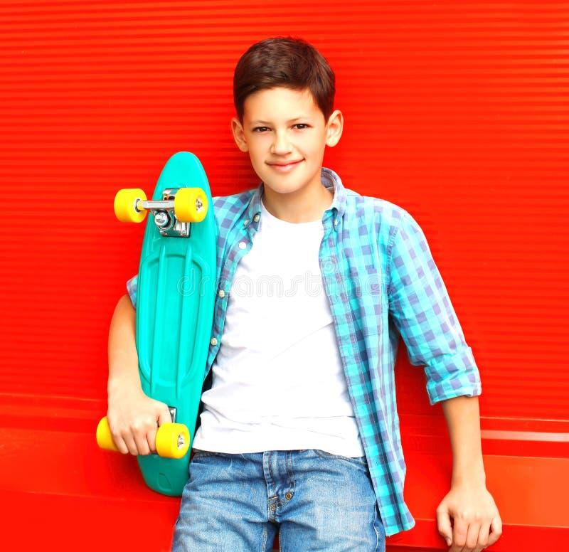 Forme o menino de sorriso do adolescente com skate em uma camisa quadriculado fotos de stock