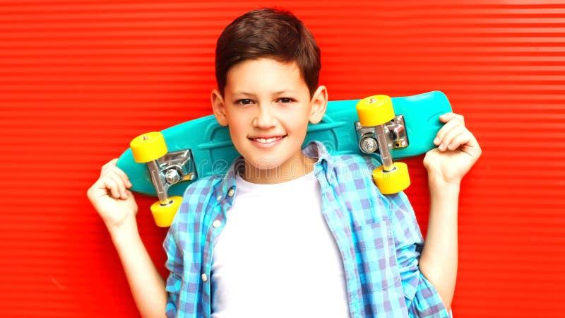 Forme o menino de sorriso do adolescente do retrato com o skate no vermelho fotografia de stock