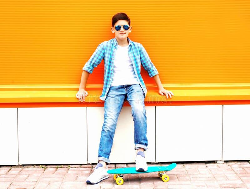 Forme o menino do adolescente com poses do skate em uma laranja colorida imagens de stock