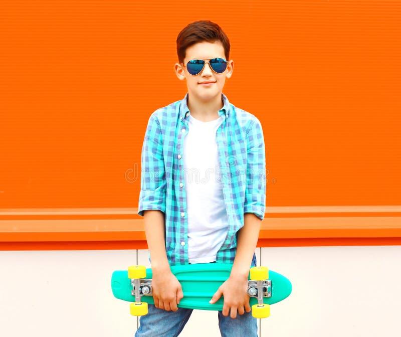 Forme o menino do adolescente com o skate na laranja colorida foto de stock
