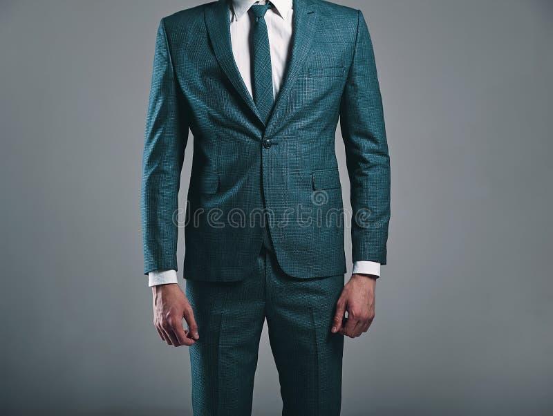 Forme o modelo à moda do homem de negócios vestido no terno verde elegante que levanta no cinza fotografia de stock