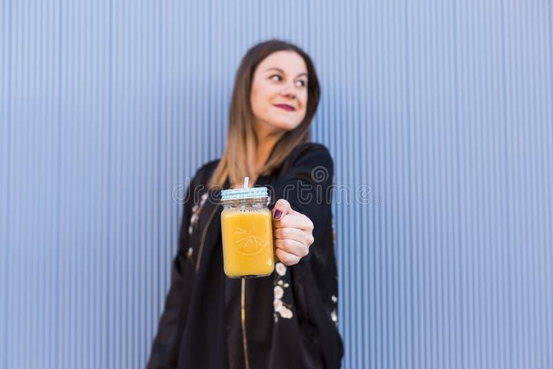 Forme o modelo bonito da mulher com o copo do suco de fruto fresco que veste a SU fotografia de stock