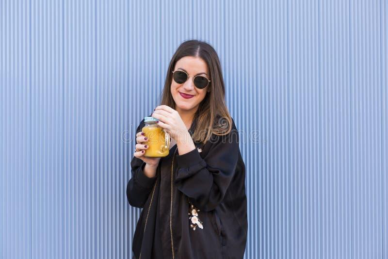 Forme o modelo bonito da mulher com o copo do suco de fruto fresco que veste a SU imagens de stock royalty free
