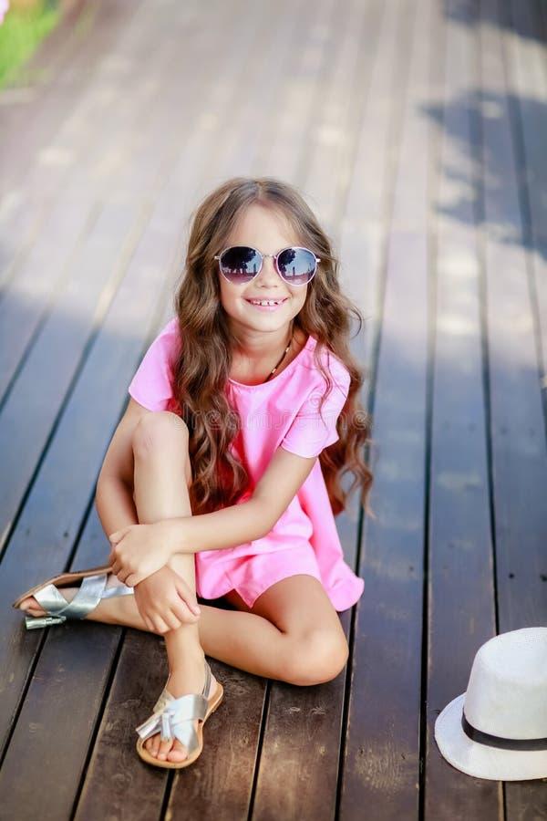 Forme o modelo da menina que veste uma camisa, um chapéu e uns óculos de sol quadriculado cor-de-rosa na cidade fotografia de stock