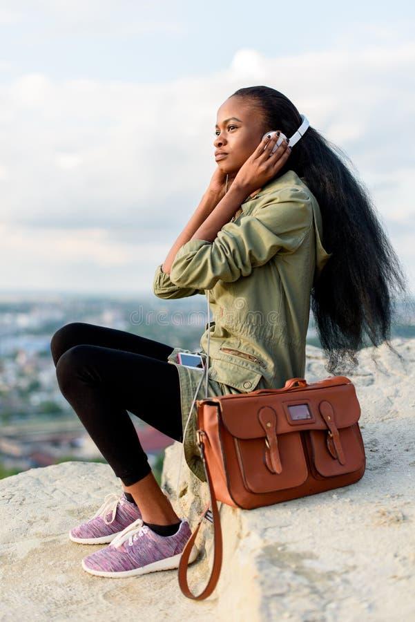 Forme o retrato da jovem mulher afro-americano bonita do moderno com smartphone e fones de ouvido que escuta a música fotos de stock