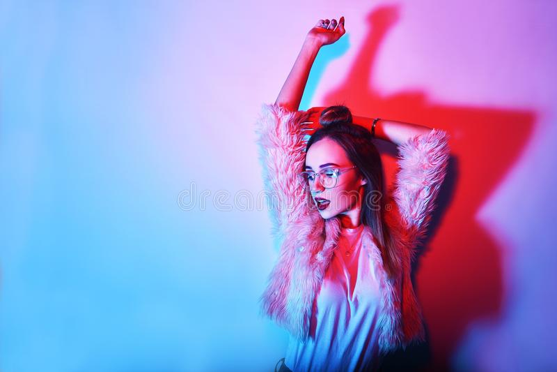 Forme o retrato da menina elegante nova nos vidros Fundo colorido, tiro do estúdio Mulher triguenha bonita dança da menina do mod fotografia de stock