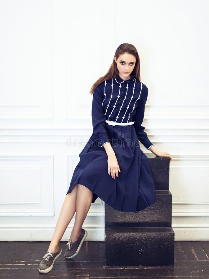 Forme o retrato da menina no vestido azul que senta-se em escadas do estúdio fotografia de stock royalty free