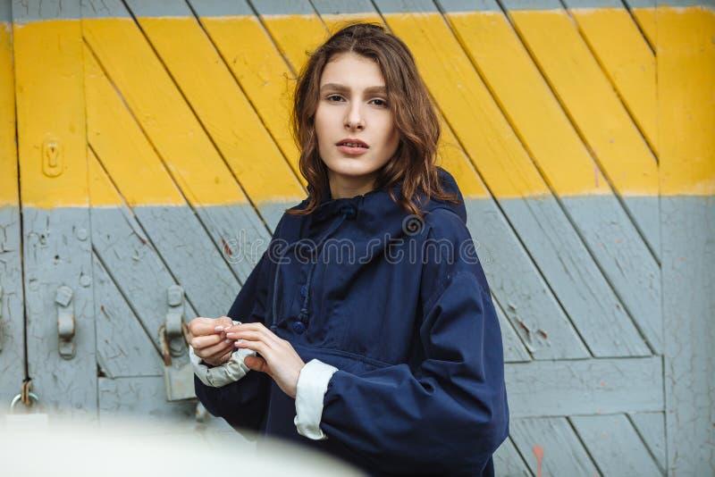Forme o retrato da mulher bonita à moda que levanta contra a porta do armazém no dia nebuloso Equipamento urbano na moda vestindo imagem de stock