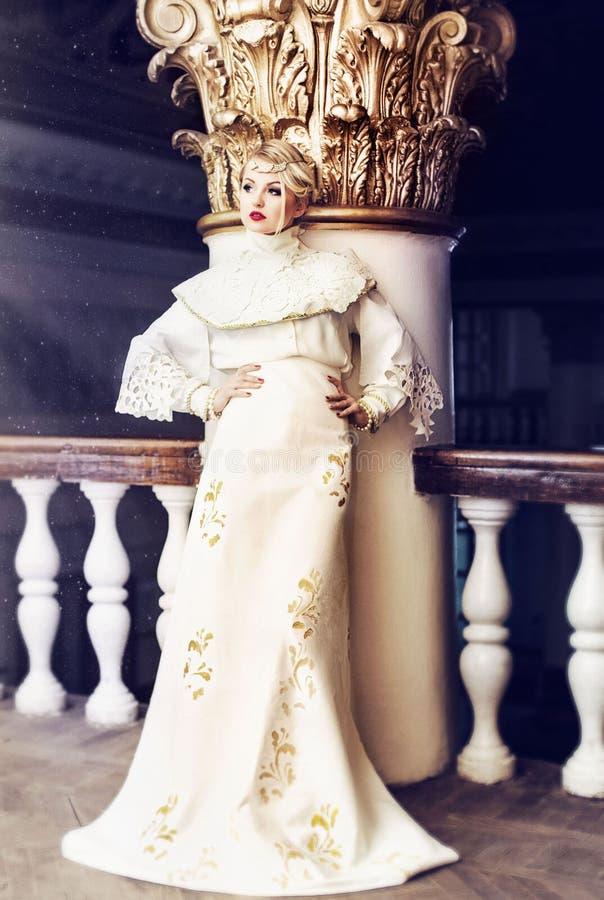 Forme o retrato da mulher bonita no vestido branco longo em um ol fotografia de stock