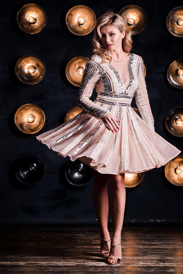 Forme o retrato da mulher elegante com cabelo magnífico Menina loura Composição perfeita Menina no vestido do ouro no fundo preto imagem de stock