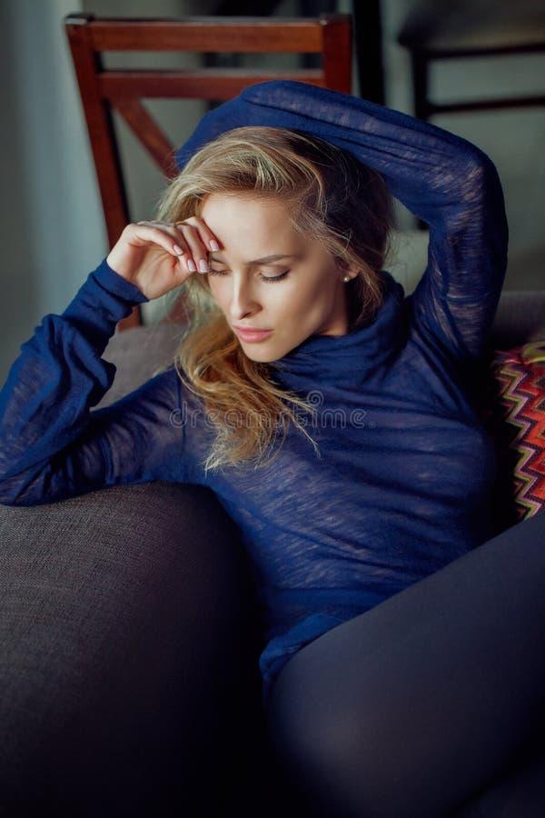 Forme o retrato da mulher elegante loura nova que senta-se no sofá fotografia de stock
