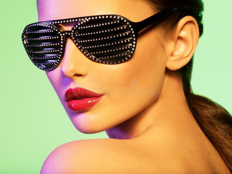 Forme o retrato da mulher que veste óculos de sol pretos com diamante imagem de stock royalty free