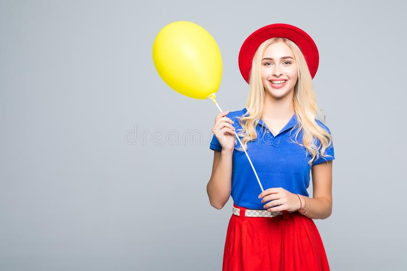 Forme o retrato de jovens mulheres bonitas na roupa e no chapéu da cor que levantam com ballons, isolado no branco fotografia de stock royalty free