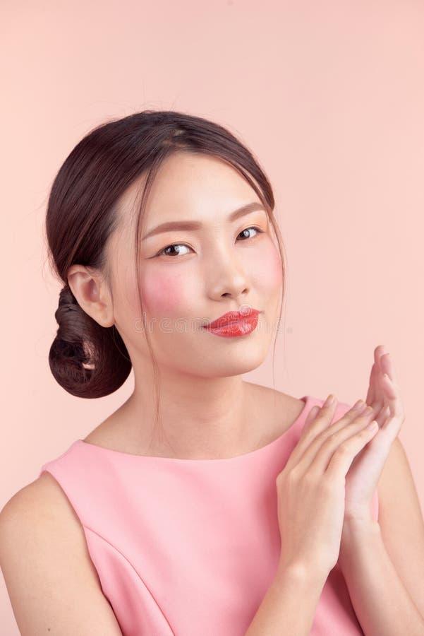 Forme o retrato de uma jovem mulher bonita em um vestido bonito sobre o fundo cor-de-rosa fotografia de stock