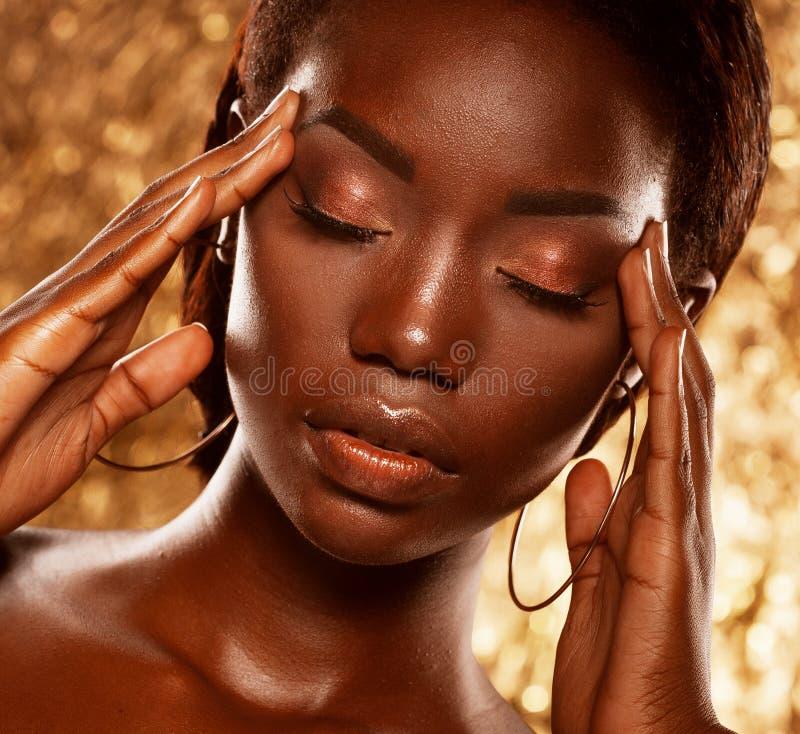 Forme o retrato do estúdio de um modelo afro-americano bonito extraordinário com os olhos fechados sobre o fundo dourado fotografia de stock royalty free