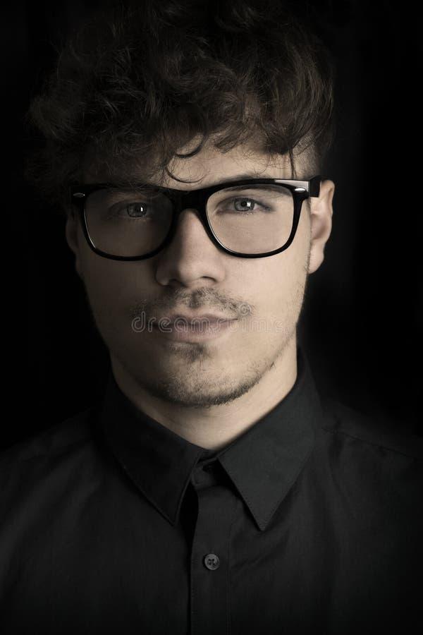 Forme o retrato escuro do homem novo 'sexy' com vidros no fundo preto Retrato do homem inteligente Indivíduo encaracolado do retr foto de stock royalty free