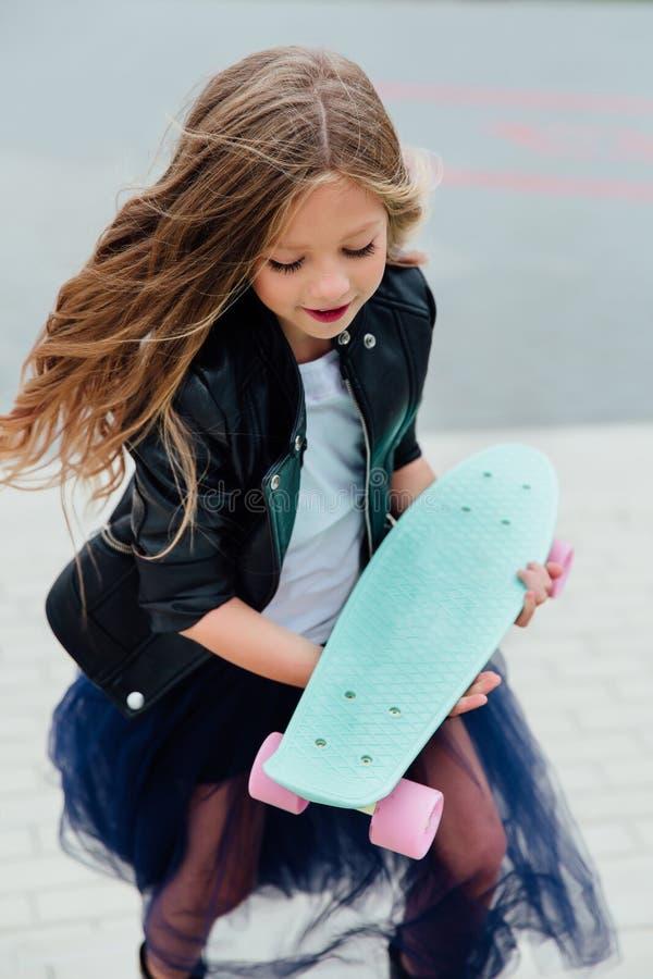 Forme o skate do schoolgirlwith da criança na cidade na rua foto de stock