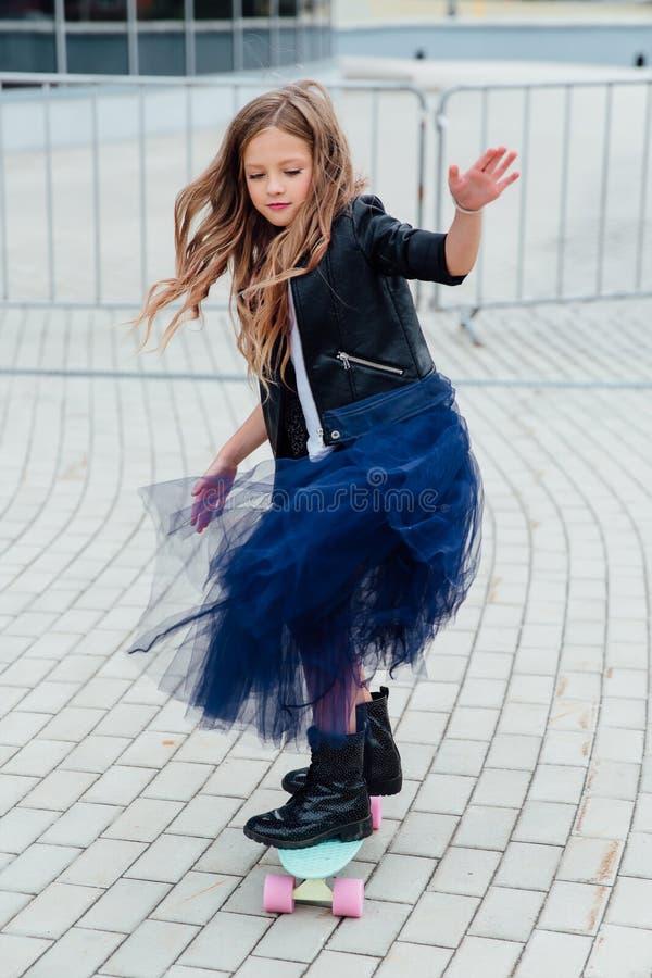 Forme o skate do schoolgirlwith da criança na cidade na rua imagem de stock
