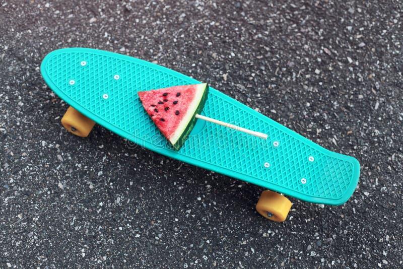 Forme o skate verde com o picolé fresco da melancia na vara sobre o pavimento textured do fundo fotos de stock