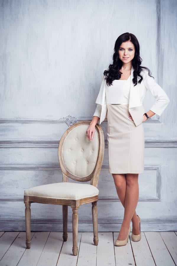 Forme o tiro da mulher bonita nova no vestido curto branco que está a cadeira antiga próxima na frente da parede branca luxuosa foto de stock
