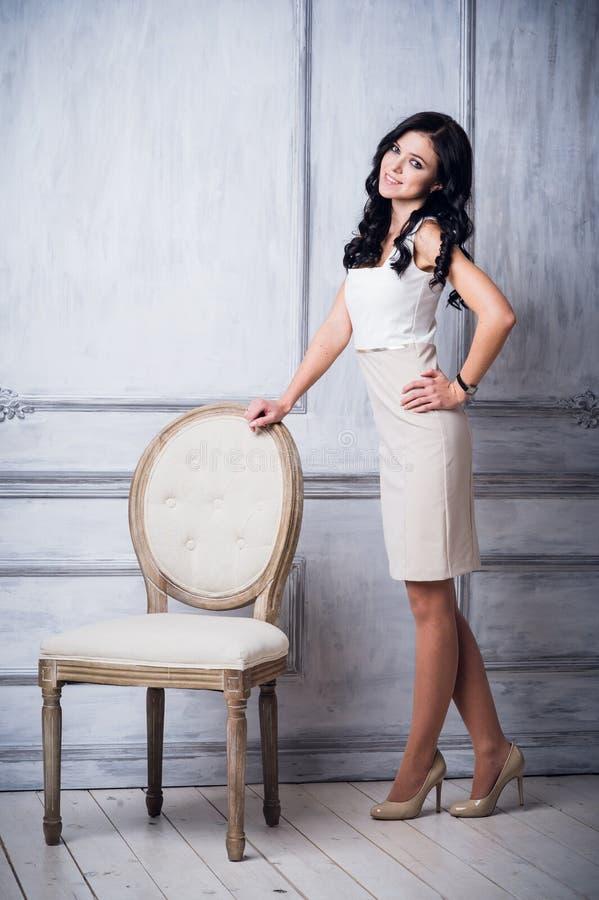 Forme o tiro da mulher bonita nova no vestido curto branco que está a cadeira antiga próxima na frente da parede branca luxuosa fotografia de stock