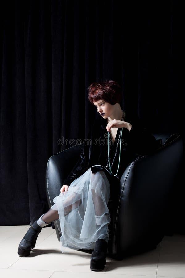 Forme o tiro de uma moça bonita com um moderno curto insolente do penteado no revestimento preto de veludo em um estúdio em um ba imagens de stock