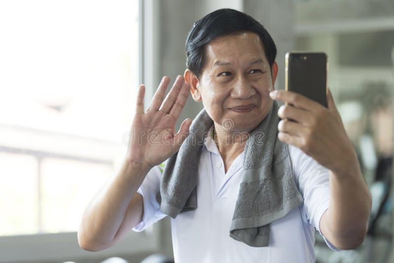 Forme physique active de sourire attrayante d'homme asiatique supérieur le gymnase et en prenant un selfie photo libre de droits