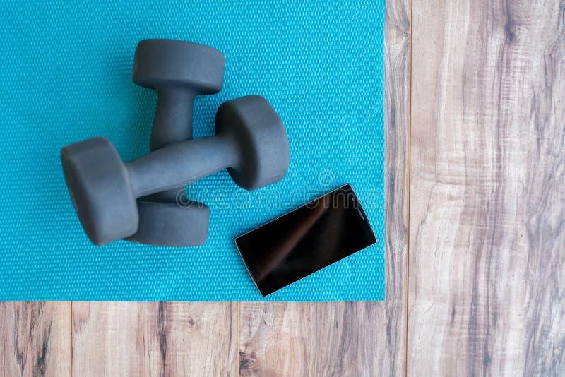 Forme physique au téléphone portable APP de tapis de yoga de maison-poids photographie stock libre de droits
