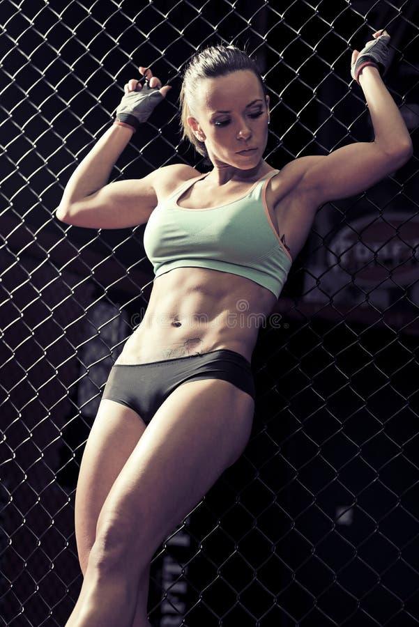 Forme physique de jeune femme dans la cage kickboxing de formation photographie stock