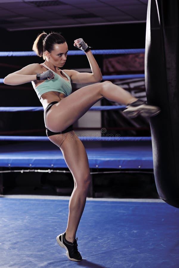 Forme physique de jeune femme donnant un coup de pied devant le sac de sable photo stock