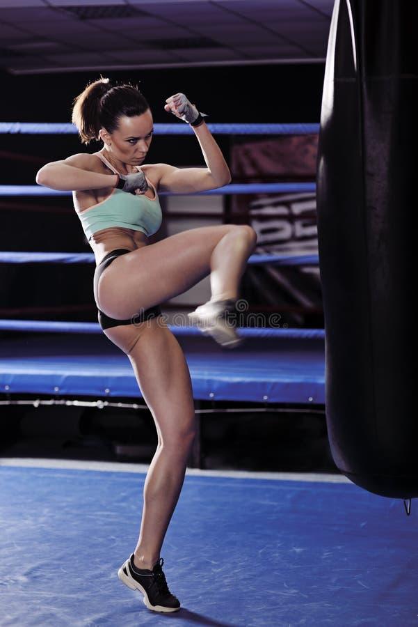 Forme physique de jeune femme donnant un coup de pied devant le sac de sable image stock