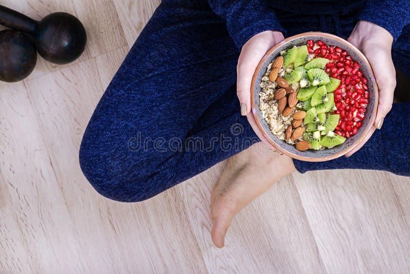 Forme physique et concept sain de mode de vie La femelle est reposante et mangeante une farine d'avoine saine après une séance d' images stock