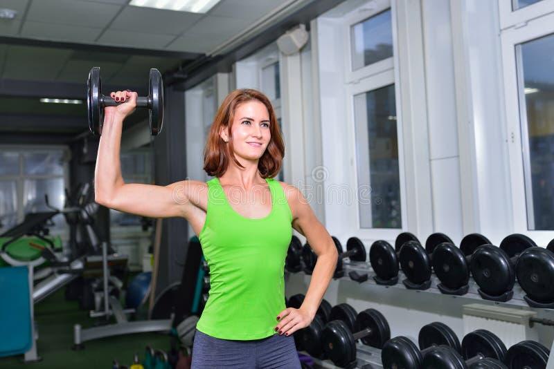 Forme physique, sport, exerçant le mode de vie - femme sportive de Moyen Âge faisant des exercices avec l'haltère au gymnase photos stock