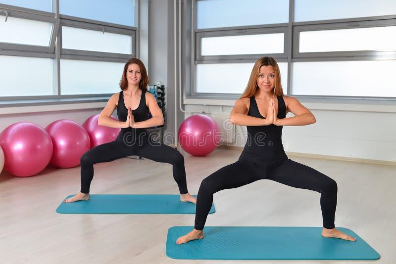 Forme physique, sport, exerçant le mode de vie - groupe féminin faisant la pratique en matière de yoga au gymnase image libre de droits