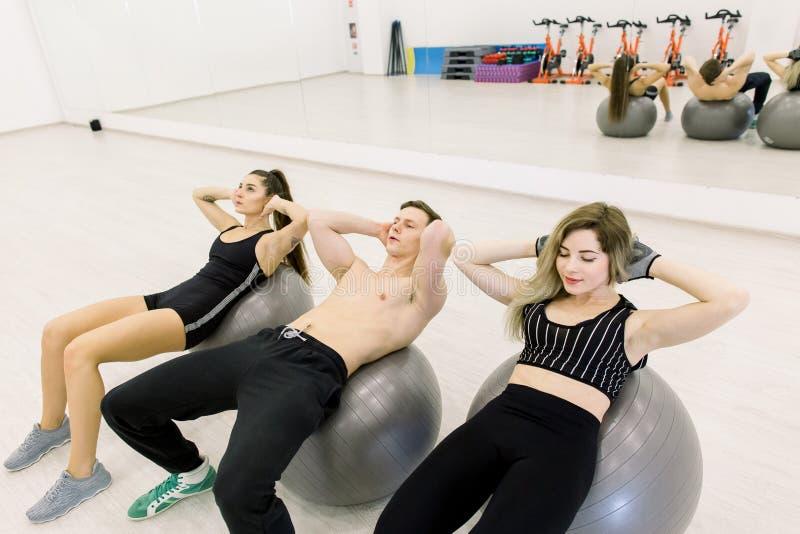 Forme physique, sport, formation et concept de personnes - filles et garçon de sourire fléchissant des muscles abdominaux avec la photos libres de droits