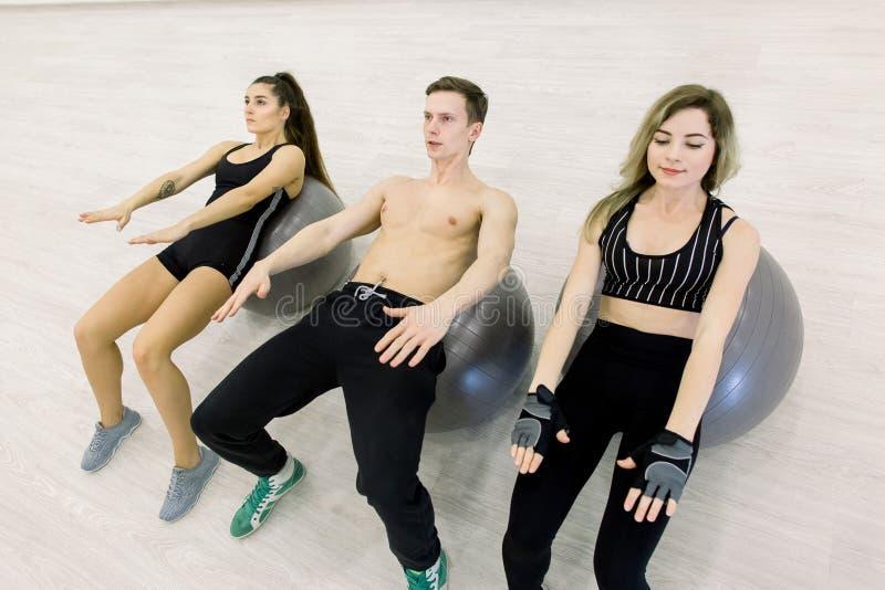Forme physique, sport, formation et concept de personnes - filles et garçon de sourire fléchissant des muscles abdominaux avec la photos stock