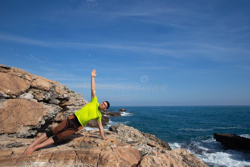 Forme physique, sport, les gens et concept de mode de vie - jeune homme faisant des exercices de yoga sur la plage à partir du do image stock